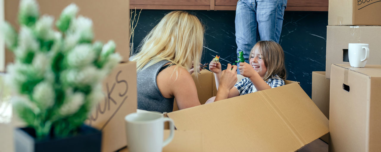 Mother and son playing sitting inside a moving box while the father looks at the mobile Family Fun Funny Happiness Happy Man Moving Unpacking Woman Boxes Boy Cardboard Home Interior House Indoors  Kid Lifestyles Living Room New Home Packing Placing Playing Real People Relocating Vertical