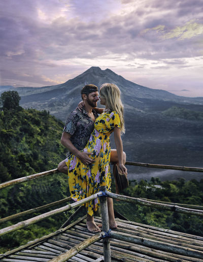 Young couple standing on railing against mountains