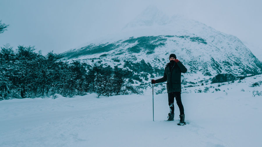Man standing on snow covered field against snowcapped mountain