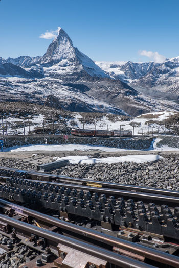 Aerial view of railroad tracks by snowcapped mountains against sky