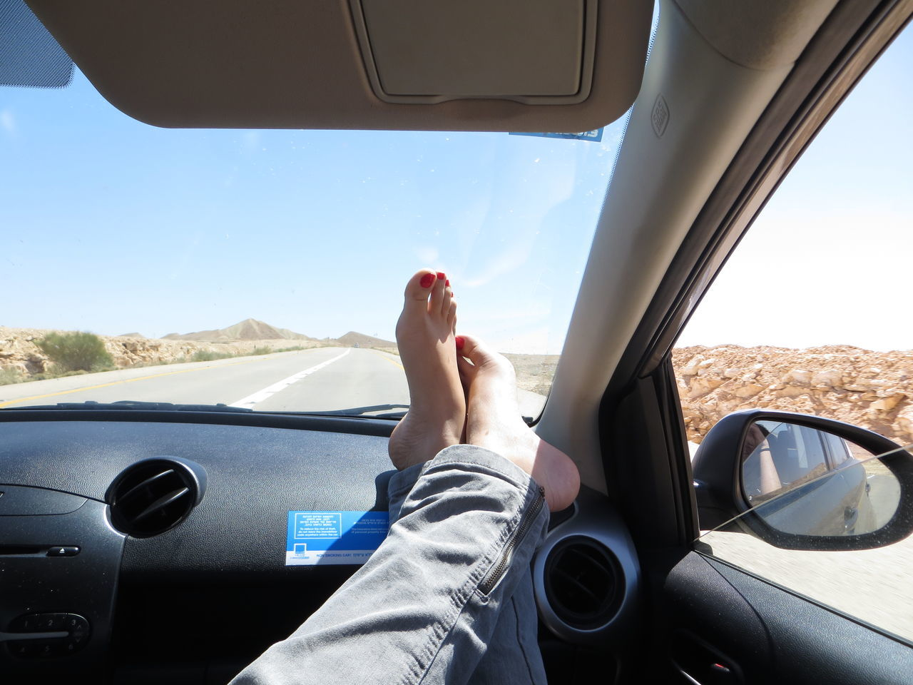 Low section of woman relaxing in car