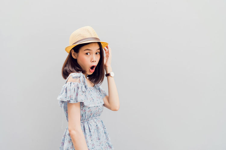 Young girl happy smile and cheerful in blue dress. Concept summer travel. One Person Hat Standing Portrait Copy Space Studio Shot Indoors  Clothing Looking At Camera Women Waist Up Looking Child Hair Childhood Front View Girls Casual Clothing Innocence Hairstyle Beautiful Woman Contemplation