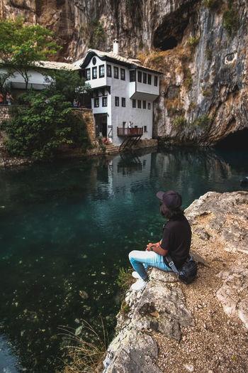Man sitting on rock by lake