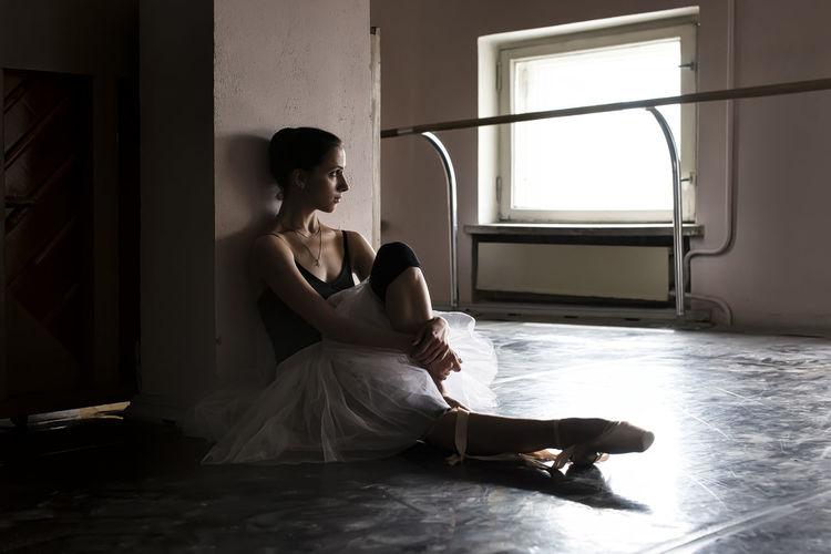 Full length of young ballet dancer sitting on floor