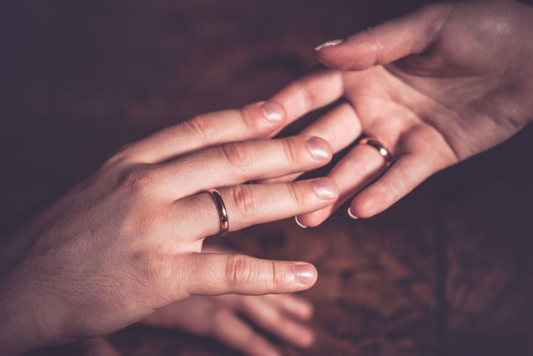 Close-up of couple with wedding rings holding hands
