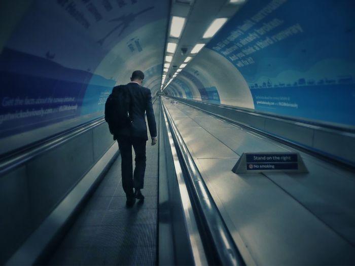 Man Walking On Escalator At Subway Station