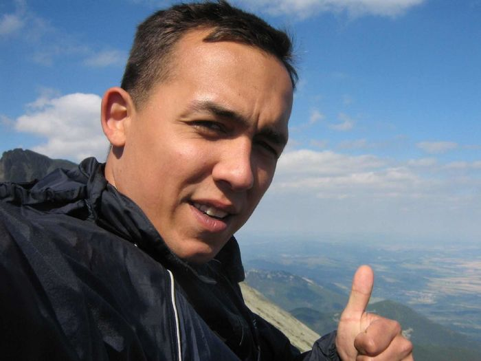 Close-up portrait of man gesturing thumbs up against landscape