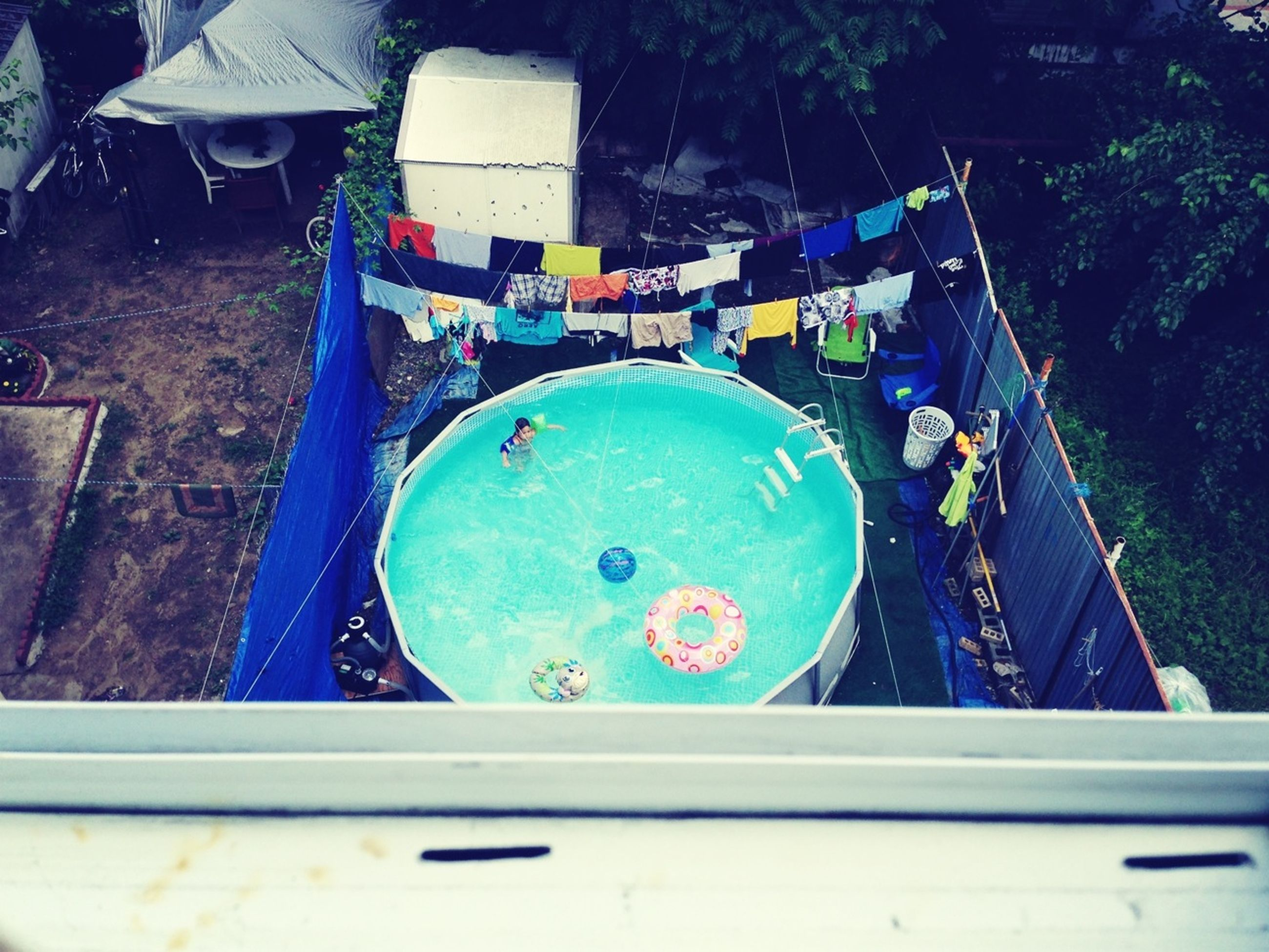 water, high angle view, blue, nautical vessel, circle, day, transportation, no people, outdoors, swimming pool, boat, tree, reflection, mode of transport, table, moored, sunlight, close-up, multi colored, built structure