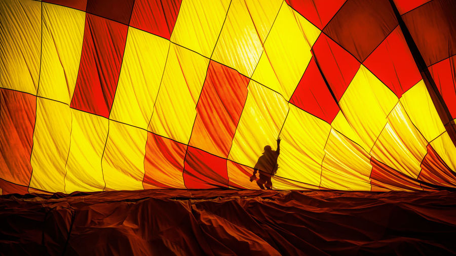 Silhouette people in hot air balloon