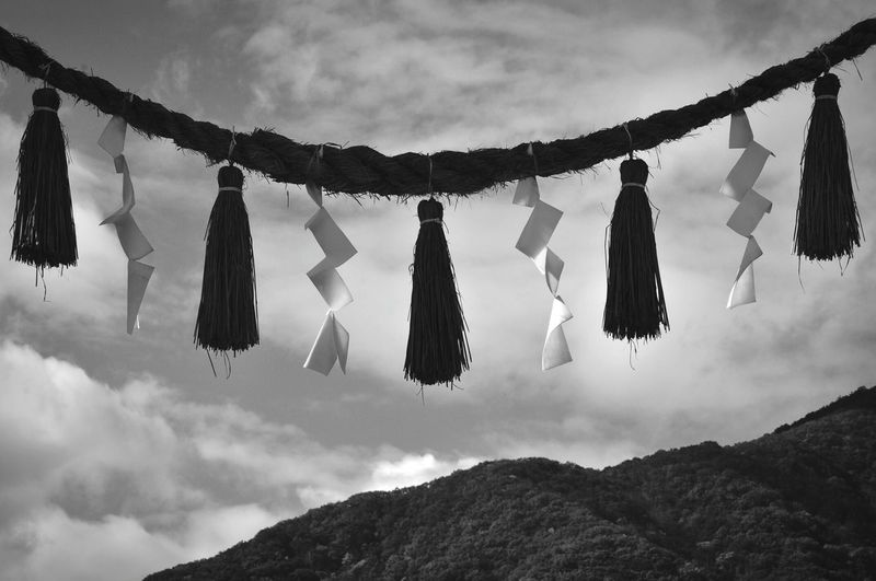 Low Angle View Of Artwork Hanging On Rope By Mountain Against Sky