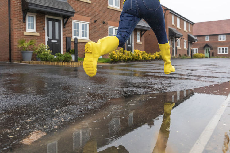 Low section of person on wet yellow outside house