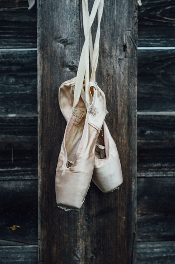 Ballet shoes hanging from wooden wall