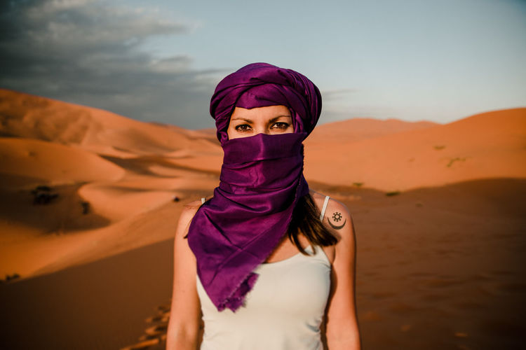 Close-up of a tourist woman wearing a purple turban looking at camera
