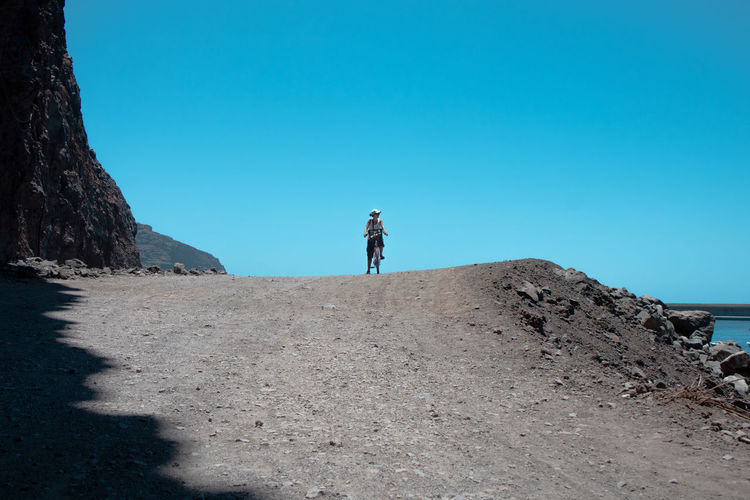 Man standing on shore against clear blue sky