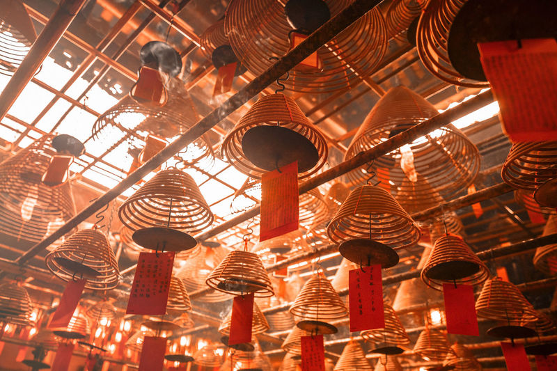 Low angle view of spiral incenses hanging in temple