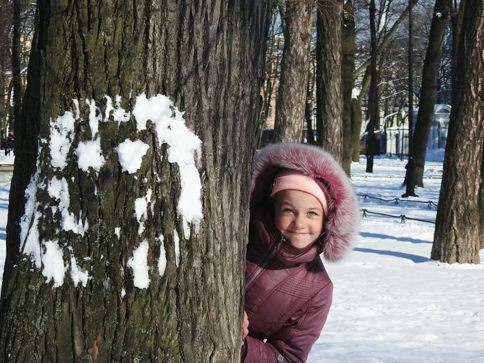 Portrait Of Smiling Girl Standing By Tree Trunk During Winter