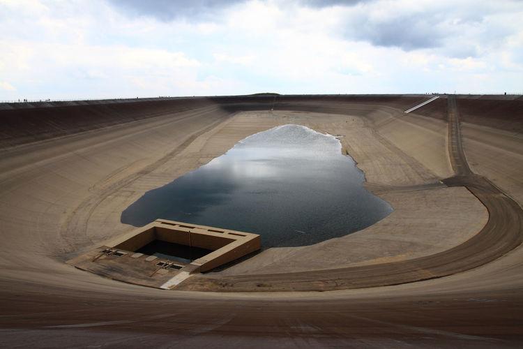 Tilt image of dam on land against sky