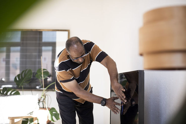 Man standing on table at home