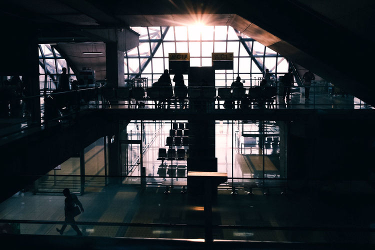 Silhouette people at railroad station platform in city against sky