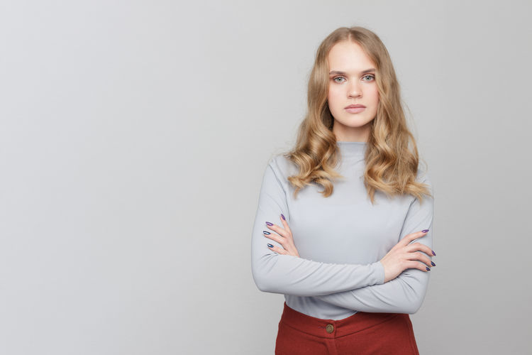 Portrait of beautiful woman with arms crossed against gray background
