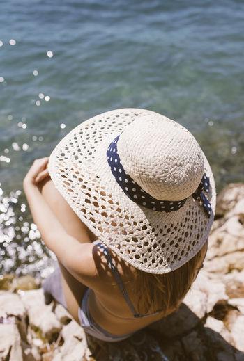 Rear view of woman wearing hat on beach
