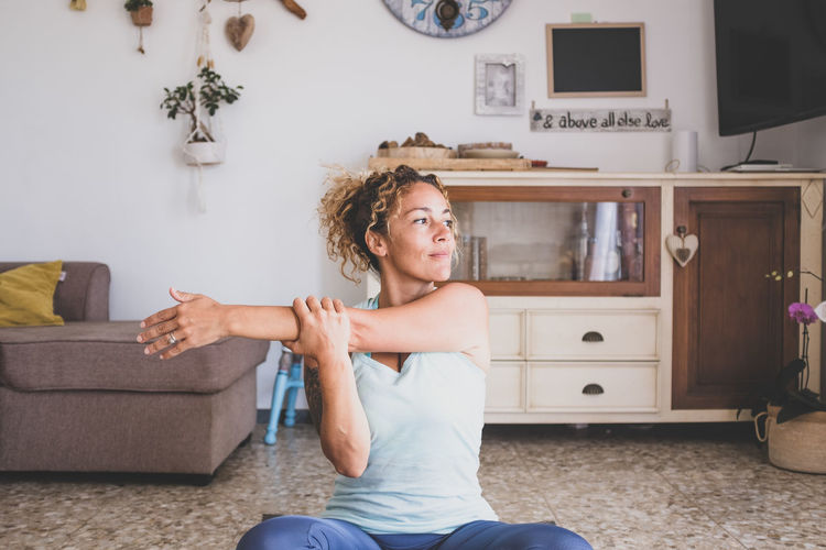 Smiling woman stretching while sitting at home
