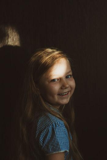 Portrait of smiling girl in dark