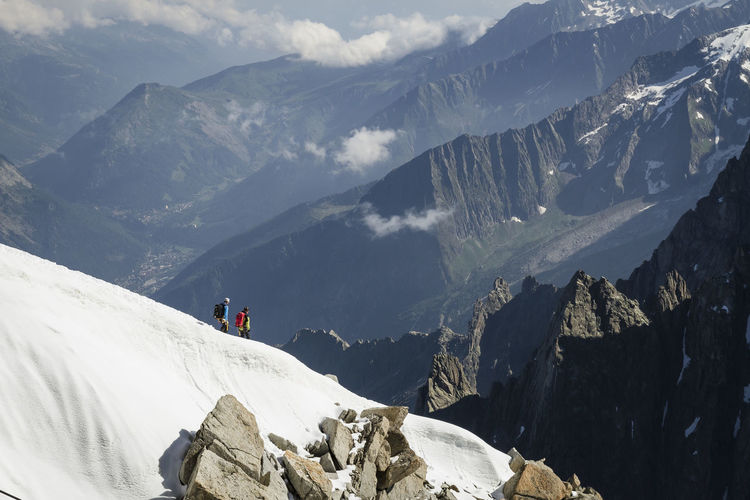 People Hiking On Snowcapped Mountains
