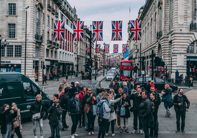Tourists gather in London, England, to take in the sights. England, UK LONDON❤ London London lifestyle London Streets Red Tourists United Kingdom City City Life City Street England Flag Flags Group Of People Londonlife Photographers Real People Red Color Tourist Destination Union Jack Union Jack Flag