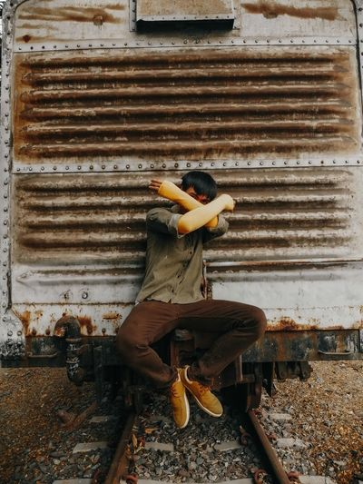 Man sitting on old train and covering face with arms
