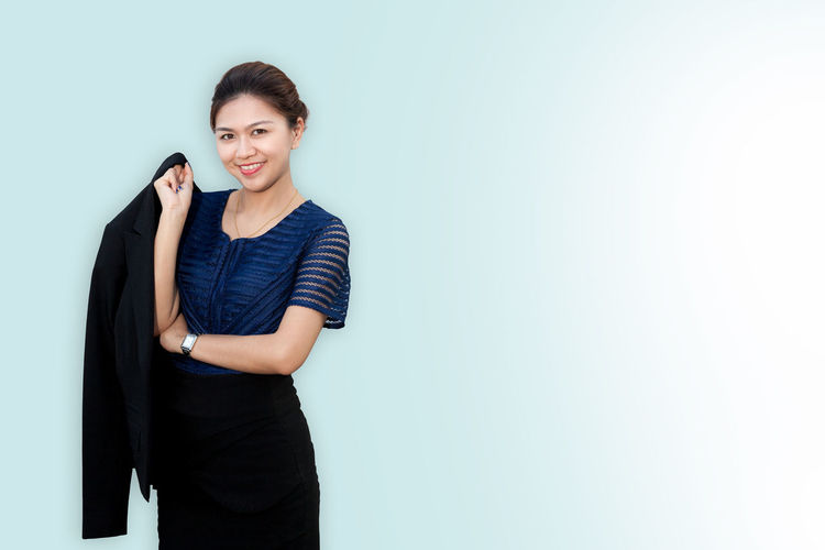 Confident business woman standing and holding her coat Asian  Isolated Portraits Stylish Suit Thai Woman Business Businesswoman Confidence  Confident  Copy Space Enjoyment Executive  Happiness Holding Jacket Looking At Camera Manager Portrait Secretary Smiling Standing Studio Shot Success