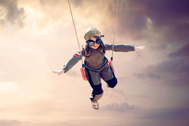 Happy child girl wearing an aviator outfit swinging and flying positive future, dreams, concept