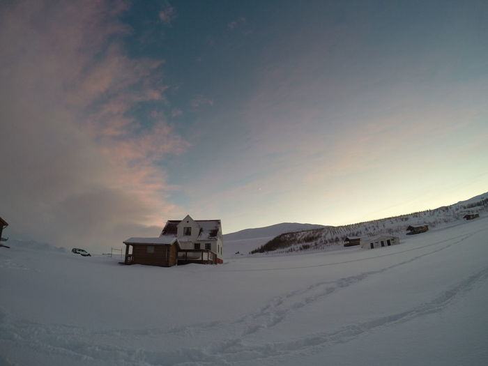 Built structure on snow covered landscape against sky during sunset