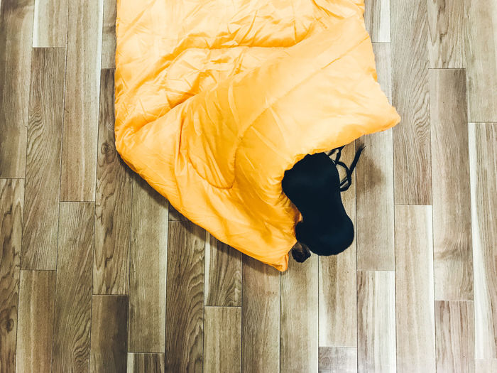 Directly Above Shot Of Miniature Pinscher With Yellow Fabric On Hardwood Floor