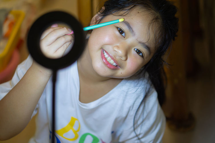 Portrait of a smiling girl holding camera at home