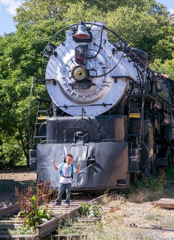 more powerful than a locomotive! this little boy pass in front of an old steam engines on display in Golden colorado at the Colorado train museum BIG Fun Golden Colorado Learning Outdooors Train Tracks USA America Colorado Train Museum Education Locomotive Steal Train Train - Vehicle Train Display Train Station Travel Destinations Kid Fun Boy Pose Play learning about trains