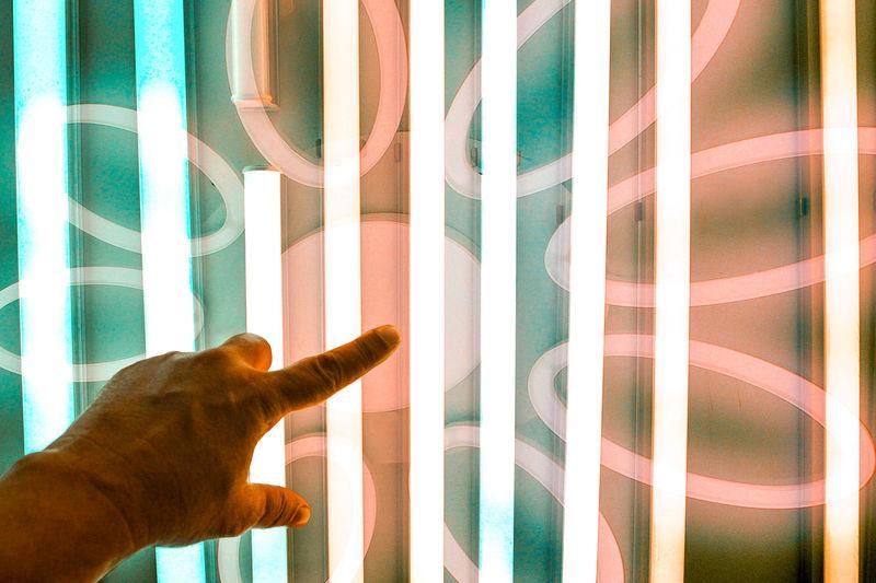Close-up of hand gesturing towards illuminated glass