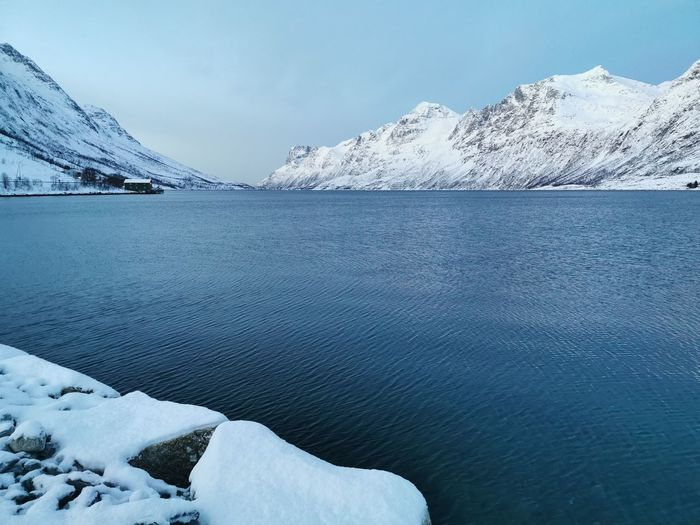 Frozen lake by snowcapped mountains against sky