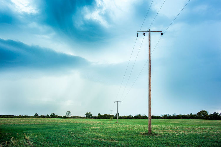 Electricity pylon on grassy field against cloudy sky