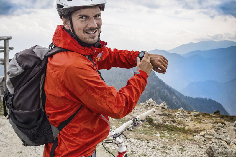 Portrait of mountain biker showing smart watch while standing on cliff