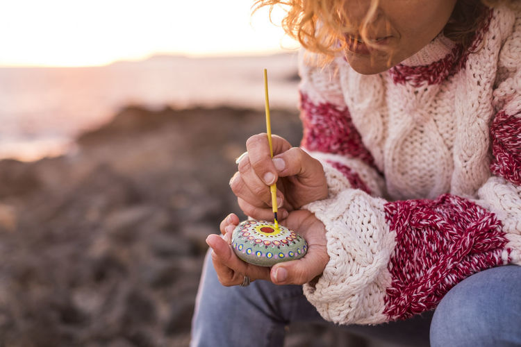 Midsection of woman painting pebble while sitting at beach during sunset