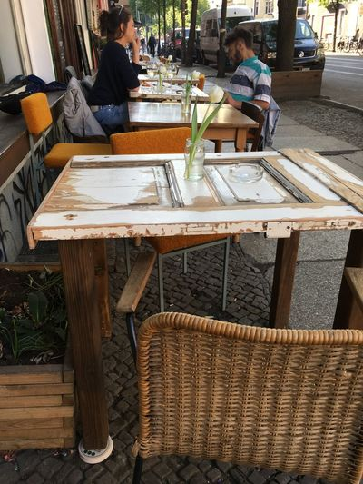 Chair Empty Chair Fresh Flowers Cafe Casual Clothing Chair Flowers Food And Drink Free Table Leisure Activity Lifestyles Outdoors People In The Background Real People Restaurant Seat Sitting Street Table Two People Young Adult