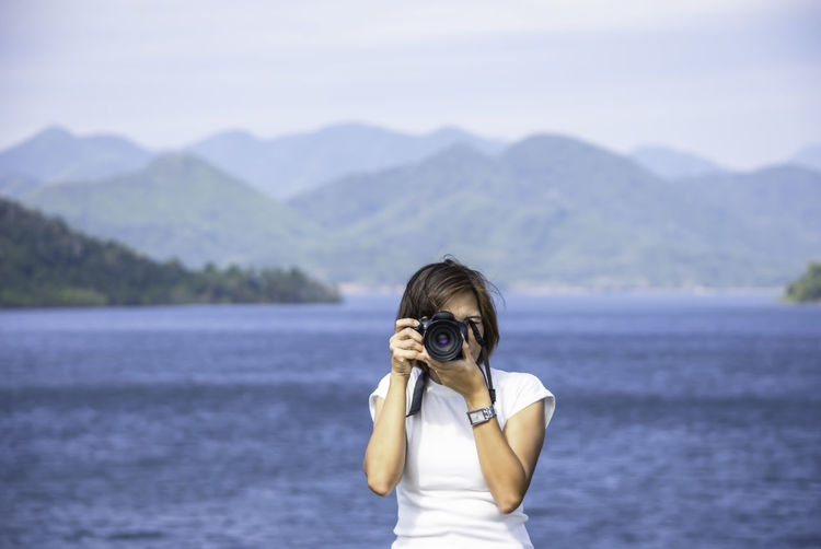 Front view of woman using camera against sea and mountains