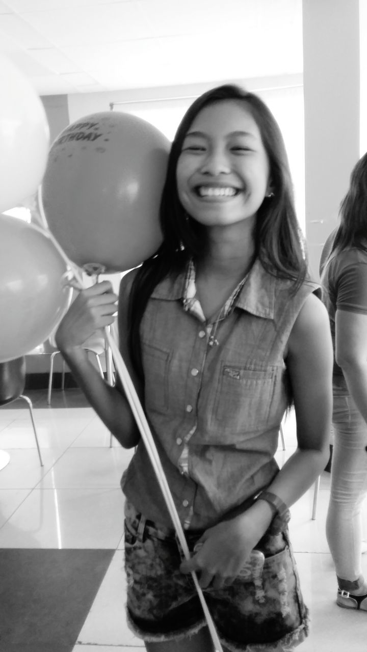 real people, smiling, indoors, happiness, balloon, holding, girls, one person, standing, childhood, young women, young adult, day, close-up