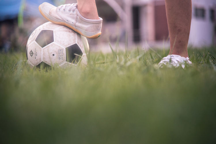Low section of person playing soccer ball on grass