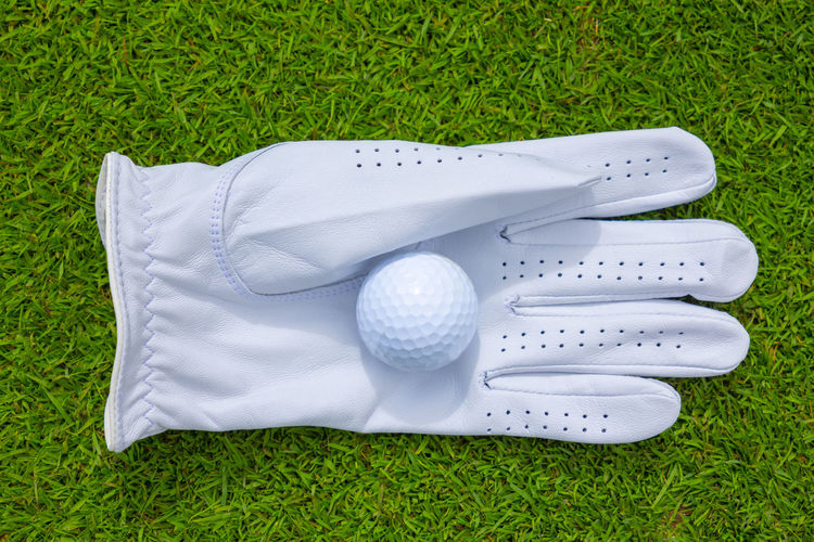 Golf Glove and Ball on the Green Grass in Switzerland. Golf Grass Golf Ball Ball Sport Green Color Golf Course White Color Leisure Activity No People Green - Golf Course High Angle View Day Close-up Still Life Golf Glove Glove Clean Directly Above Above Sports Equipment Simplicity Putting Green Ideas Hobbies