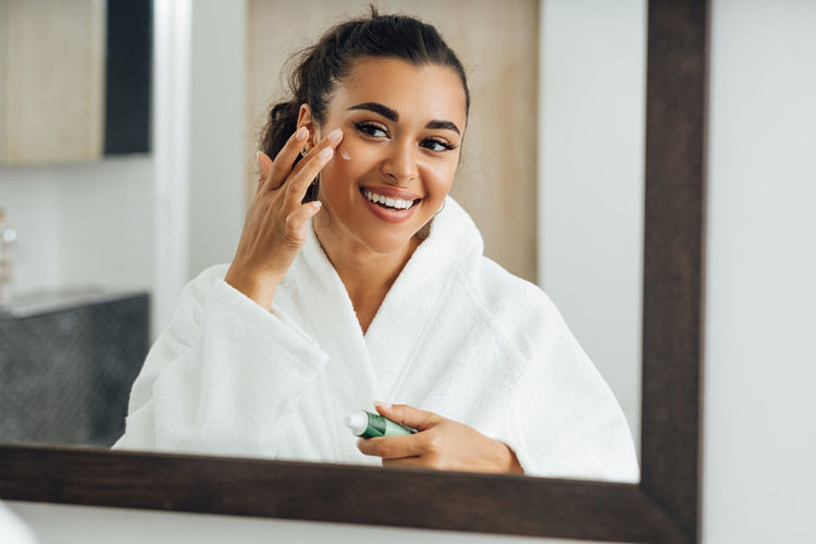 Smiling young woman applying cream on face while looking in mirror