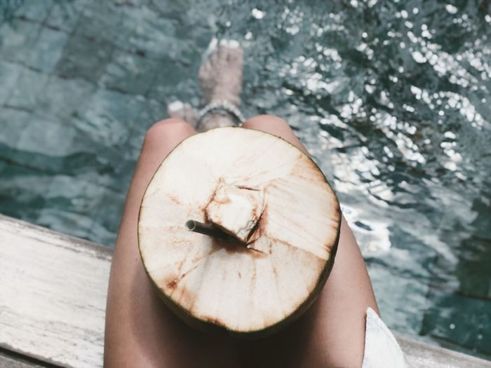 Low section of woman with coconut sitting on pier