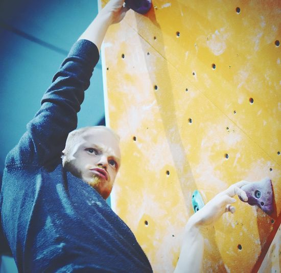 Low angle view of athlete making face while climbing rock wall in gym