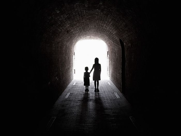 Darkness Standing Arch Architecture Built Structure Child Day Direction Full Length Horror Photography Light At The End Of The Tunnel Outdoor People Real People Silhouette The Way Forward Thriller Togetherness Tunnel Two People Wall - Building Feature